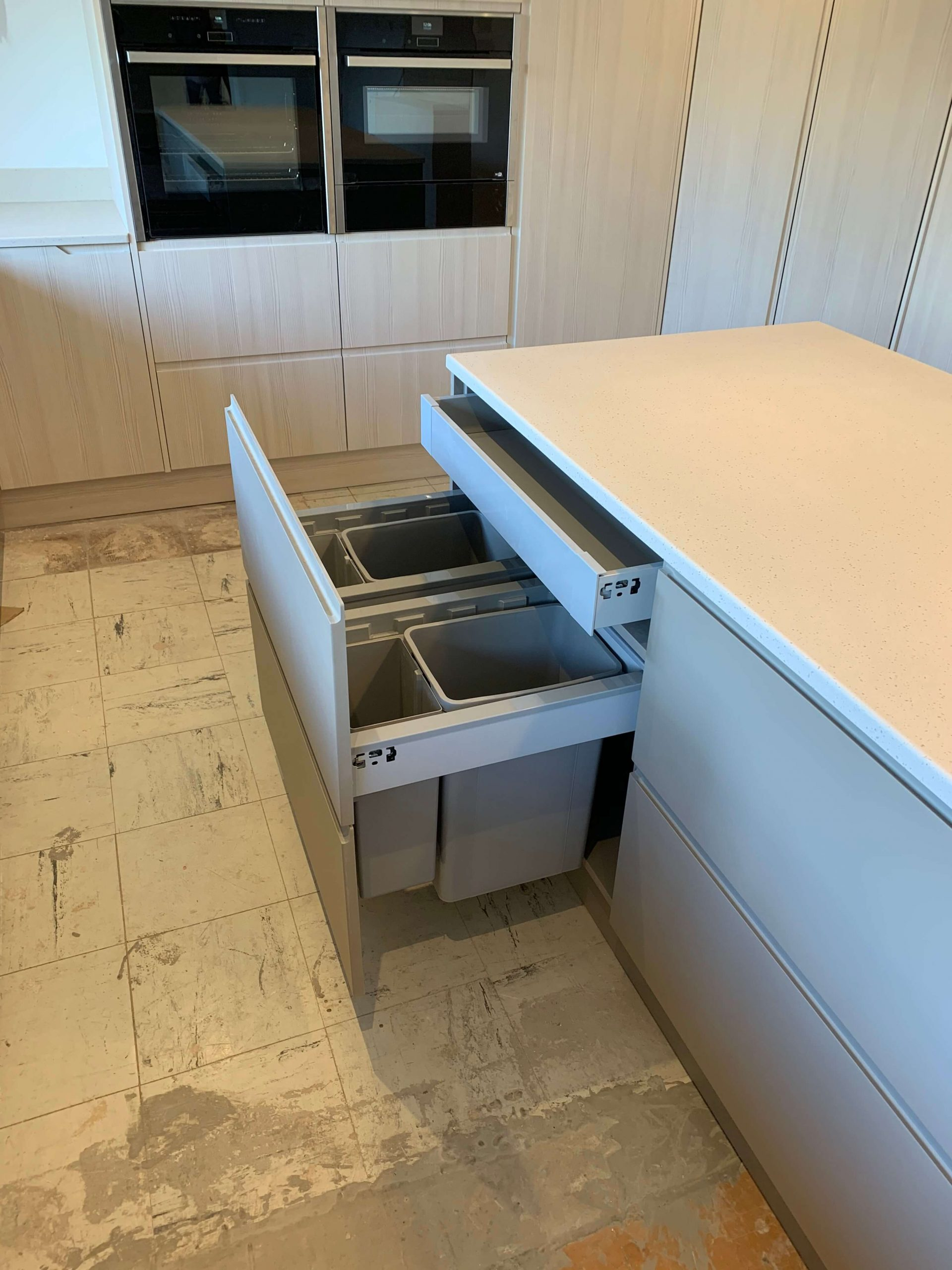Twin waste bins with secret drawer above